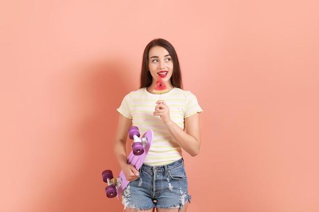 Mulher jovem e bonita com uma fatia de melancia fresca e um skate na cor de fundo