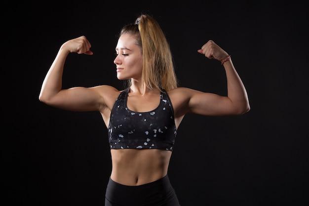 Mulher jovem e bonita com uma figura atlética em um fundo preto