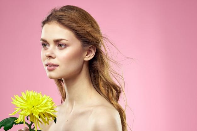 Mulher jovem e bonita com uma flor amarela posando