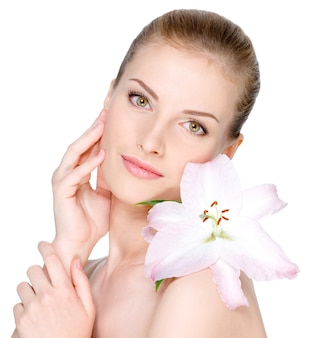 Mulher jovem e bonita com uma flor no ombro, acariciando o rosto claro - isolado no branco