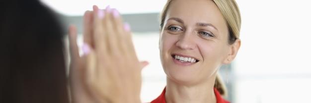 Mulher jovem e bonita com uma jaqueta vermelha dando mais cinco para um colega de escritório