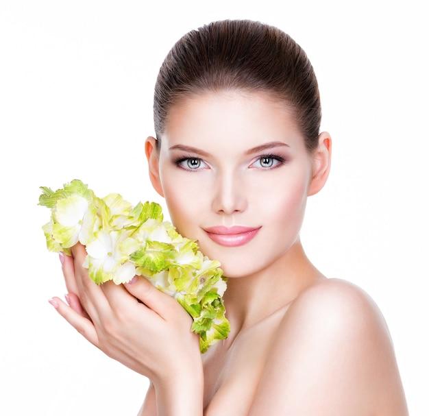 Mulher jovem e bonita com uma pele limpa e saudável, segurando uma flor nas mãos -