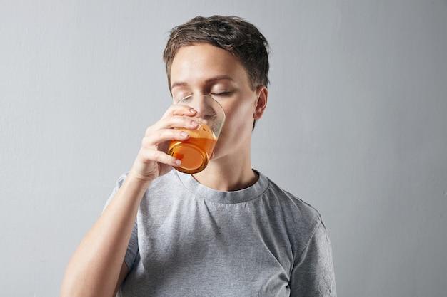 Mulher jovem e bonita com uma pele perfeita e saudável, bebendo sonhadoramente seu suco de laranja de cenoura orgânico fresco
