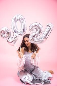 Mulher jovem e bonita com uma roupa festiva prateada em uma parede rosa posando enquanto está sentada e segurando balões prateados para o conceito de ano novo