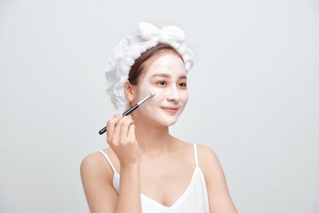 Mulher jovem e bonita com uma toalha enrolada na cabeça e aplicando máscara facial