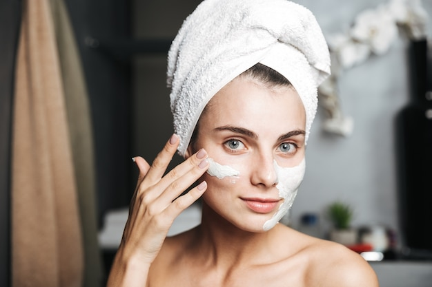 Mulher jovem e bonita com uma toalha enrolada na cabeça e aplicando máscara no banheiro