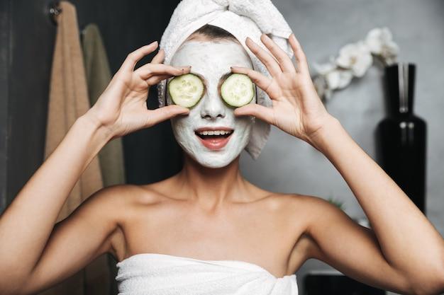 Mulher jovem e bonita com uma toalha enrolada na cabeça e máscara facial