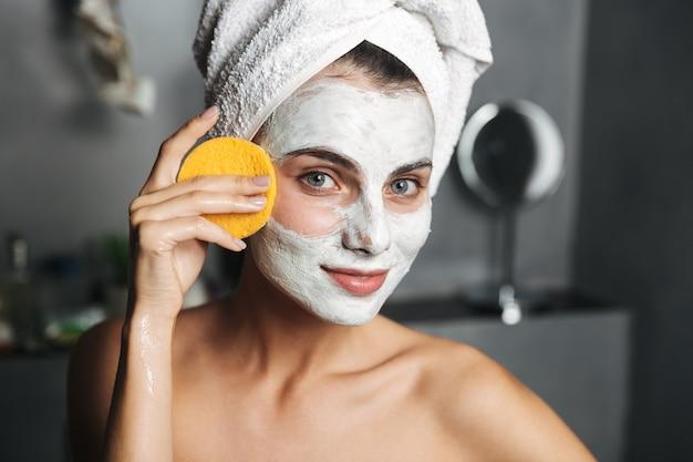 Mulher jovem e bonita com uma toalha enrolada na cabeça, removendo a máscara facial com uma esponja no banheiro