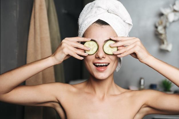 Mulher jovem e bonita com uma toalha enrolada na cabeça, segurando fatias de pepino no rosto no banheiro