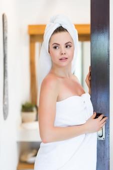 Mulher jovem e bonita com uma toalha na cabeça e com um jaleco branco se preparando para tomar banho. procedimentos de banho
