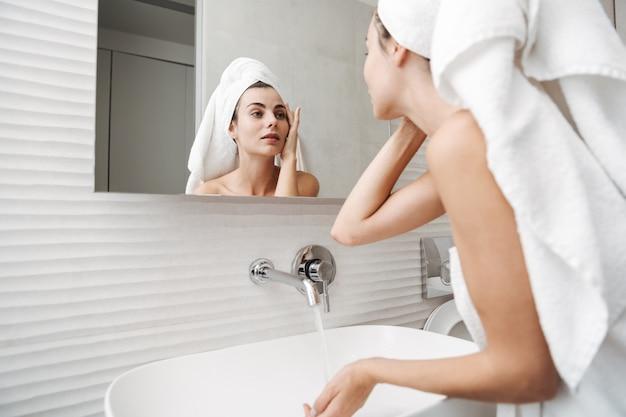 Mulher jovem e bonita com uma toalha na cabeça em pé no banheiro, examinando seu rosto no espelho