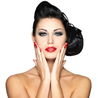 Mulher jovem e bonita com unhas vermelhas e maquiagem fashion
