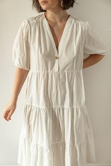 Mulher jovem e bonita com vestido de verão branco contra a parede. conceito de design de moda mínimo