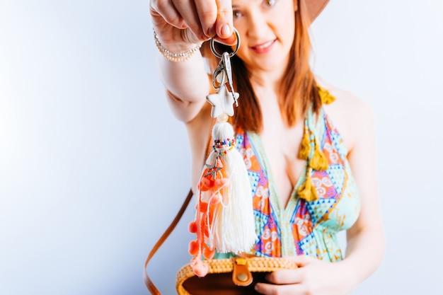 Mulher jovem e bonita com vestido de verão de chapéu de praia mostrando as chaves do apartamento alugado. conceito de aluguel de verão