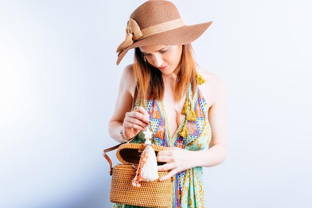 Mulher jovem e bonita com vestido de verão de chapéu de praia, retirando as chaves de um apartamento alugado. conceito de aluguel de verão