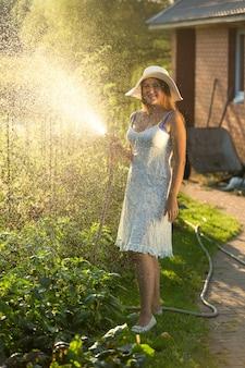 Mulher jovem e bonita com vestido de verão, desfrutando de um jardim de rega com mangueira