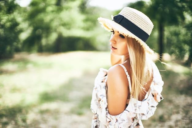 Mulher jovem e bonita com vestido de verão e chapéu de palha posando ao ar livre