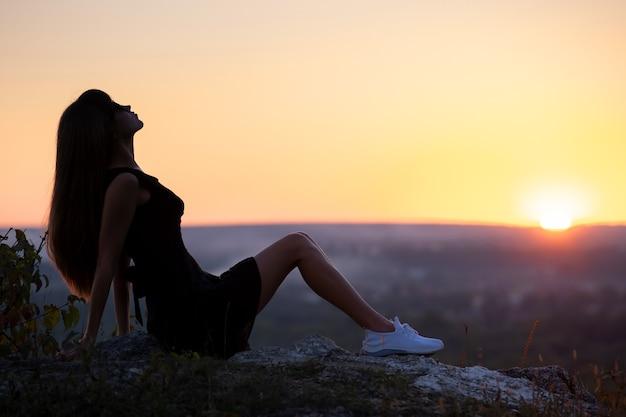 Mulher jovem e bonita com vestido preto curto de verão, sentada em uma rocha relaxante ao ar livre ao pôr do sol. mulher elegante, aproveitando a noite quente na natureza.