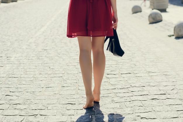 Mulher jovem e bonita com vestido vermelho, andando pela cidade sem sapatos, ela está segurando o salto alto na mão. foto de close-up das pernas compridas com os pés descalços de uma mulher contra a estrada, vista de trás