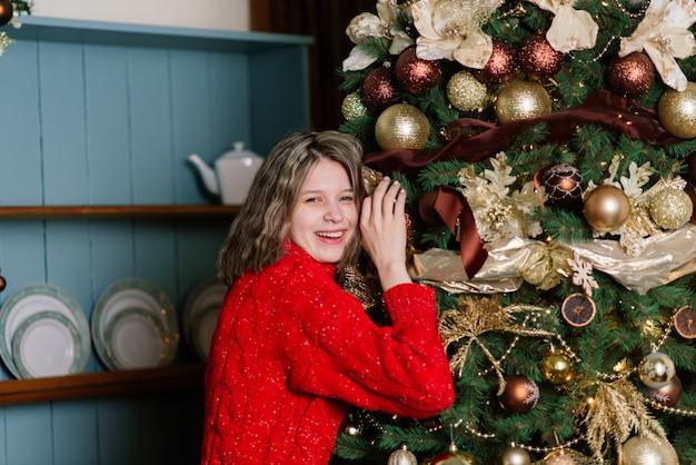 Mulher jovem e bonita comemorando o natal em casa, se divertindo enquanto abre os presentes