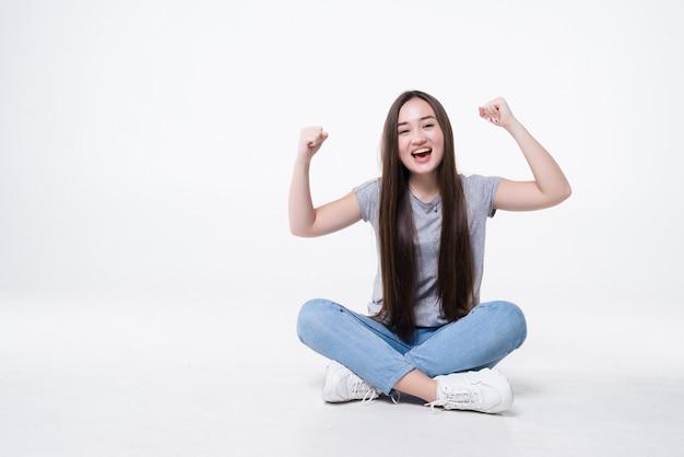 Mulher jovem e bonita comemorando o sucesso sentada no chão, isolada na parede branca