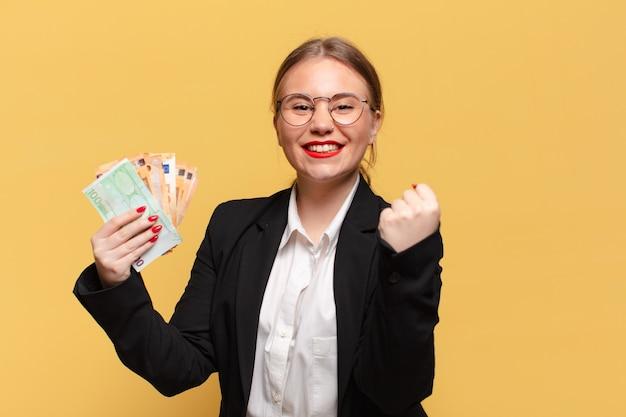 Mulher jovem e bonita comemorando um conceito de notas de euro de sucesso