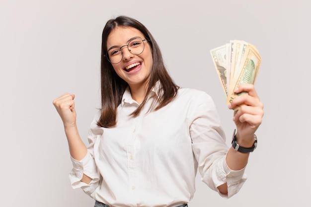 Mulher jovem e bonita comemorando uma vitória bem-sucedida e segurando notas de dólar
