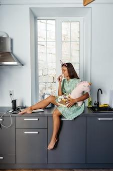 Mulher jovem e bonita comendo bolo na cozinha moderna.