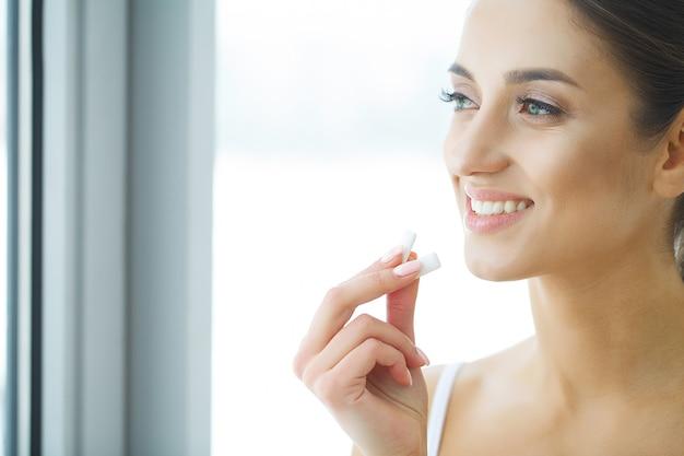 Mulher jovem e bonita comendo chiclete, sorrindo