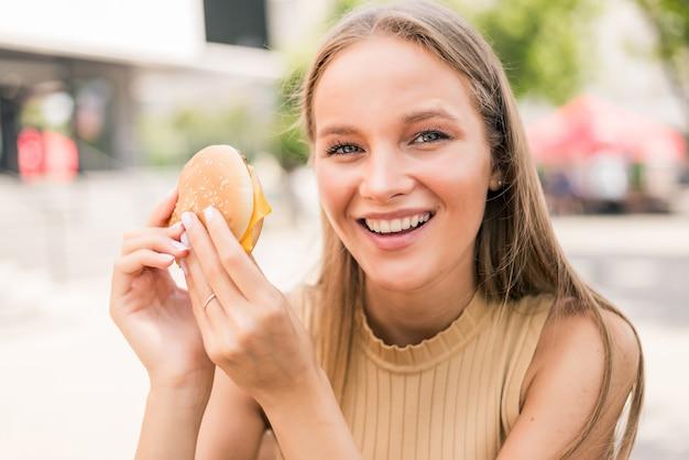 Mulher jovem e bonita comendo hambúrguer em um café de rua