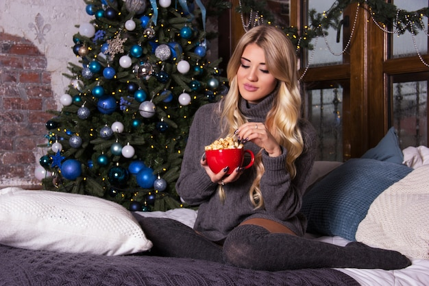 Mulher jovem e bonita comendo pipoca em casa perto da árvore de natal