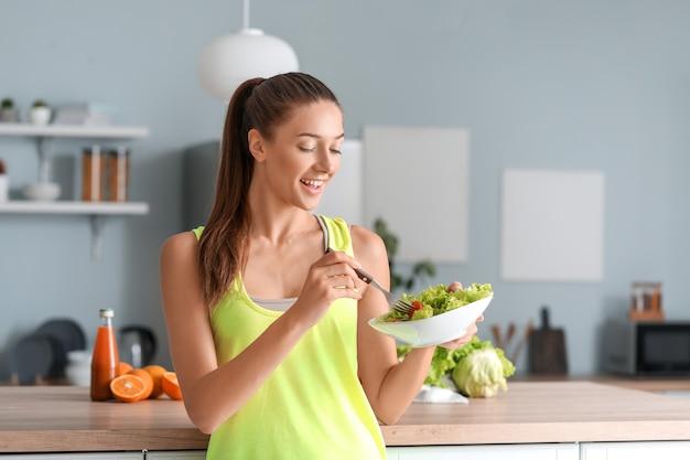 Mulher jovem e bonita comendo salada de legumes na cozinha