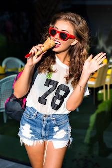 Mulher jovem e bonita comendo um grande sorvete doce em óculos de sol vermelhos, shorts, bolsa esportiva no ombro, do lado de fora no verão.