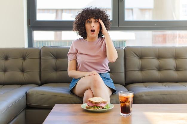 Mulher jovem e bonita comendo um sanduíche sentada em um sofá em casa