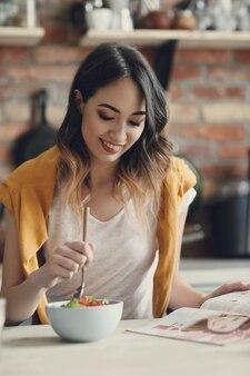 Mulher jovem e bonita comendo uma salada saudável e lendo uma revista