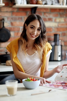 Mulher jovem e bonita comendo uma salada saudável