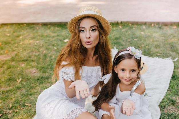 Mulher jovem e bonita, compartilhando o amor com o mundo, posando para uma foto no piquenique. duas irmãs incríveis em trajes brancos semelhantes enviando beijos no ar relaxando na grama pela manhã.