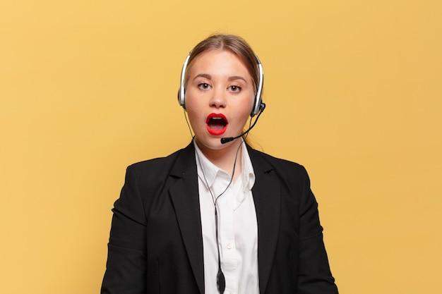 Mulher jovem e bonita. conceito de operador de telemarketing de expressão chocado ou surpreso