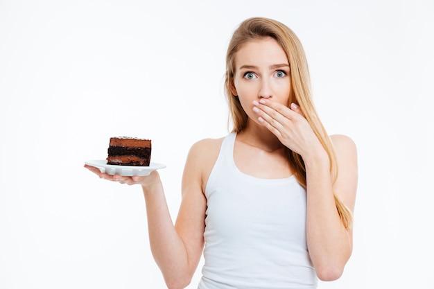 Mulher jovem e bonita confusa em dieta segurando um pedaço de bolo de chocolate sobre fundo branco