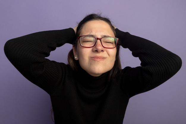 Mulher jovem e bonita confusa em uma blusa de gola alta preta e óculos de mãos dadas na cabeça com os olhos fechados em pé sobre a parede roxa