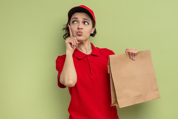 Mulher jovem e bonita confusa, entregadora de alimentos, segurando uma embalagem de papel para comida e olhando para cima