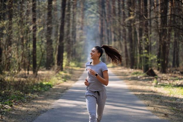Mulher jovem e bonita correndo em um parque verde em um dia ensolarado de verão