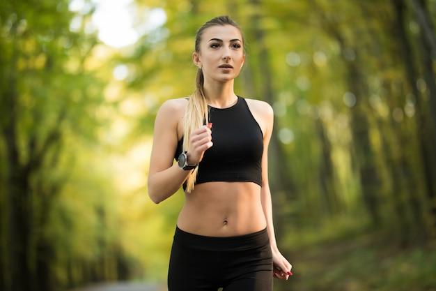 Mulher jovem e bonita correndo no parque no verão