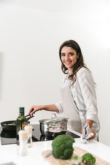 Mulher jovem e bonita cozinhando um jantar saudável em uma panela na cozinha