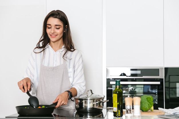 Mulher jovem e bonita cozinhando um jantar saudável na cozinha, usando uma frigideira