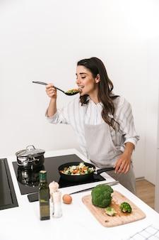 Mulher jovem e bonita cozinhando um jantar saudável na cozinha
