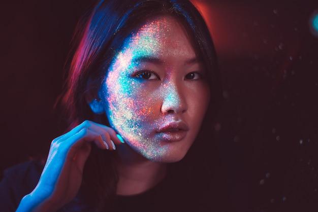 Mulher jovem e bonita dançando e fazendo festa com pintura fluorescente no rosto. retratos faciais de néon