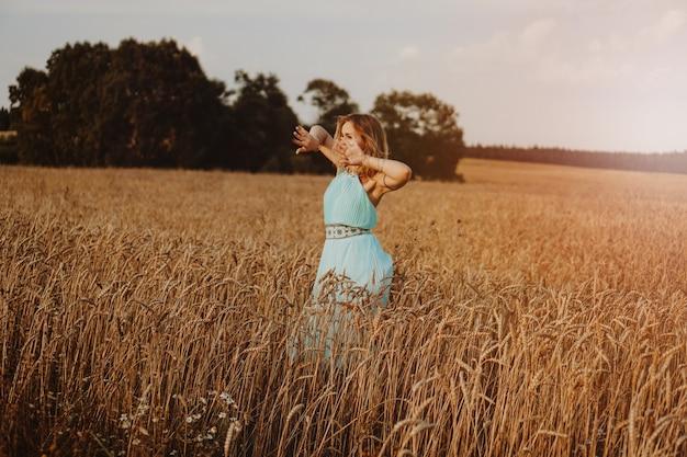 Mulher jovem e bonita dançando no campo ao pôr do sol. imagem borrada