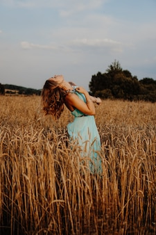 Mulher jovem e bonita dançando no campo ao pôr do sol