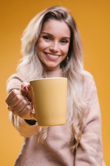 Mulher jovem e bonita dando café e olhando para a câmera